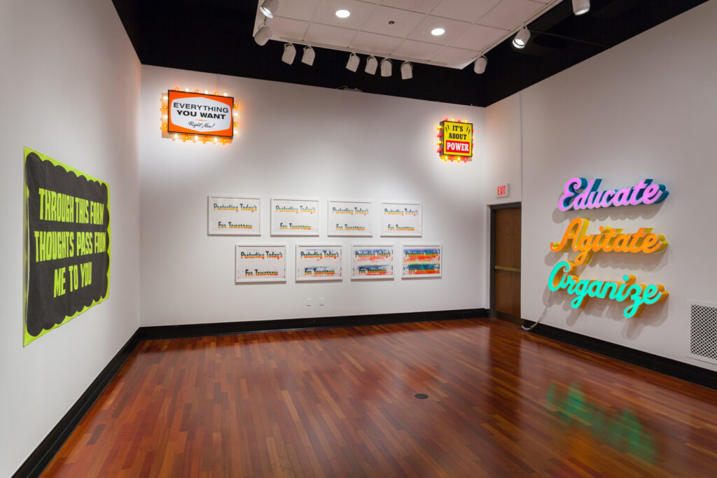 Gallery installation view of artworks that are reminiscent of billboards and posters