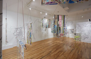 gallery exhibition featuring patchworked paintings hung on the walls and from the ceiling