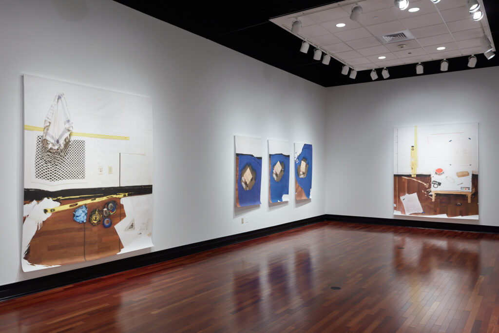 gallery exhibition featuring large digital prints pinned to the walls