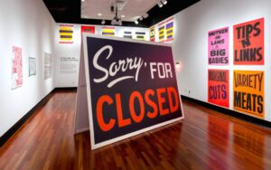 exhibition of signage art showing billboard with words Sorry for Closed in the middle of an art gallery