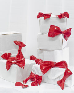 shiny red bows adorn a pile of wrapped white boxes